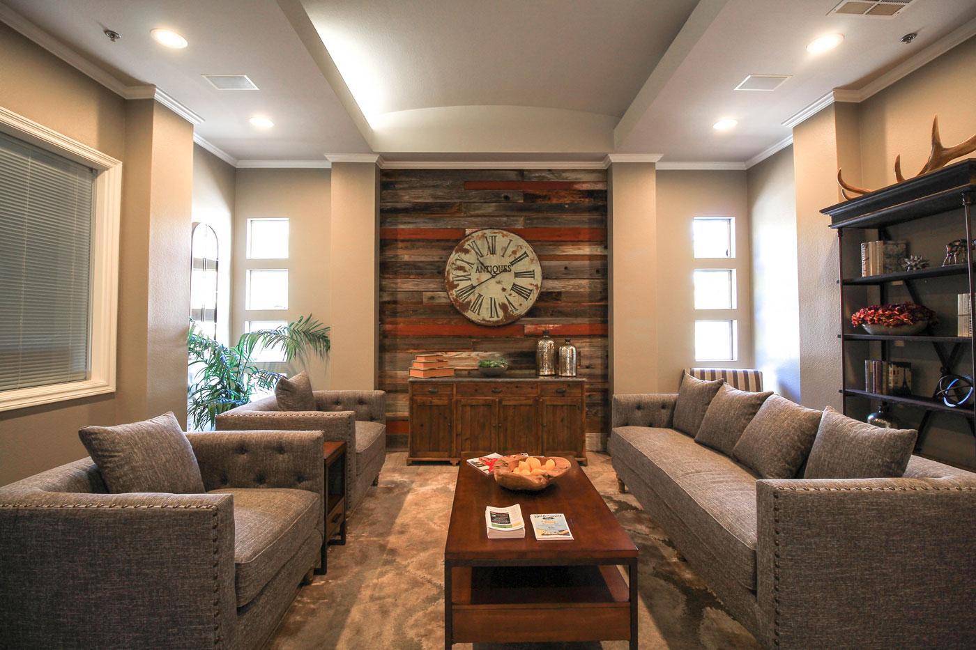 Lounge room with grey couches and clock on wall at San Tropez in Las Vegas.