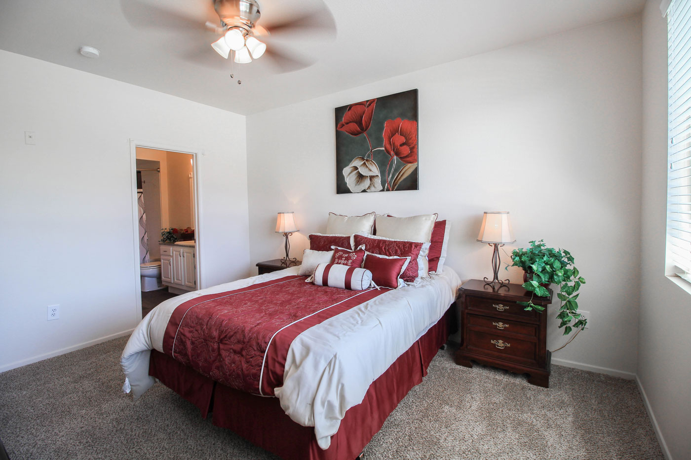 Bedroom with queen bed and red floral decor and side table lamps.